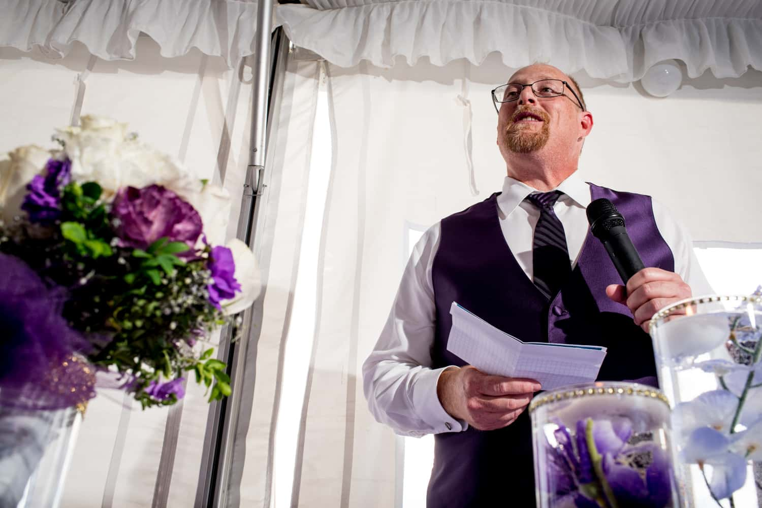 Groomsman giving a speech wearing a purple vest