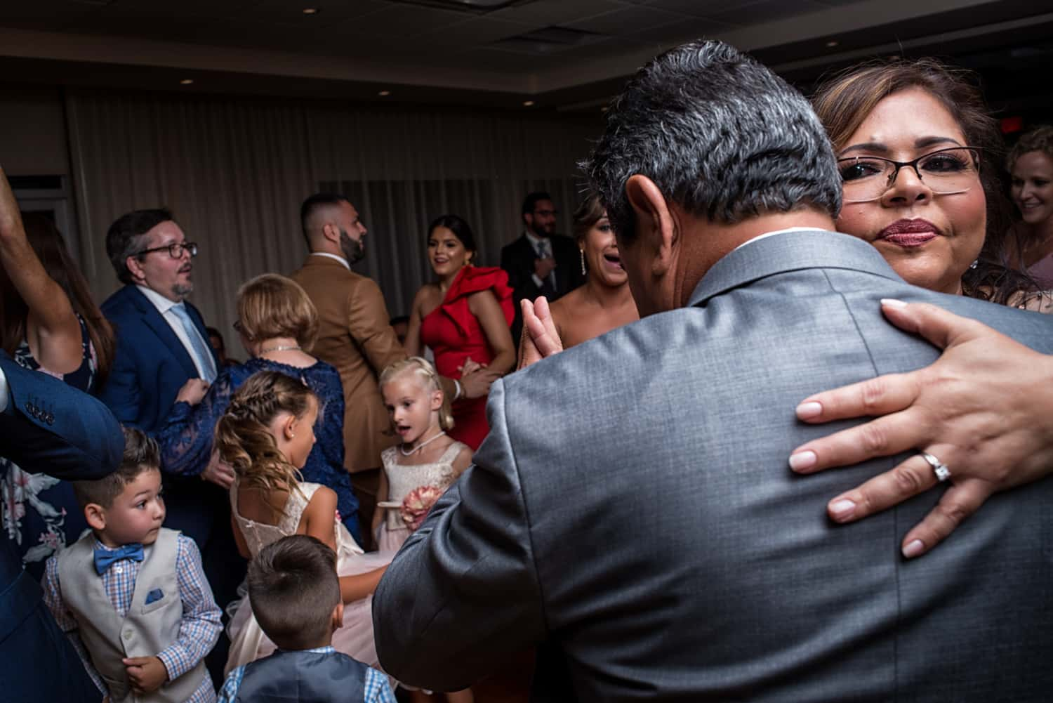 Couple dancing at wedding reception with children playing around them
