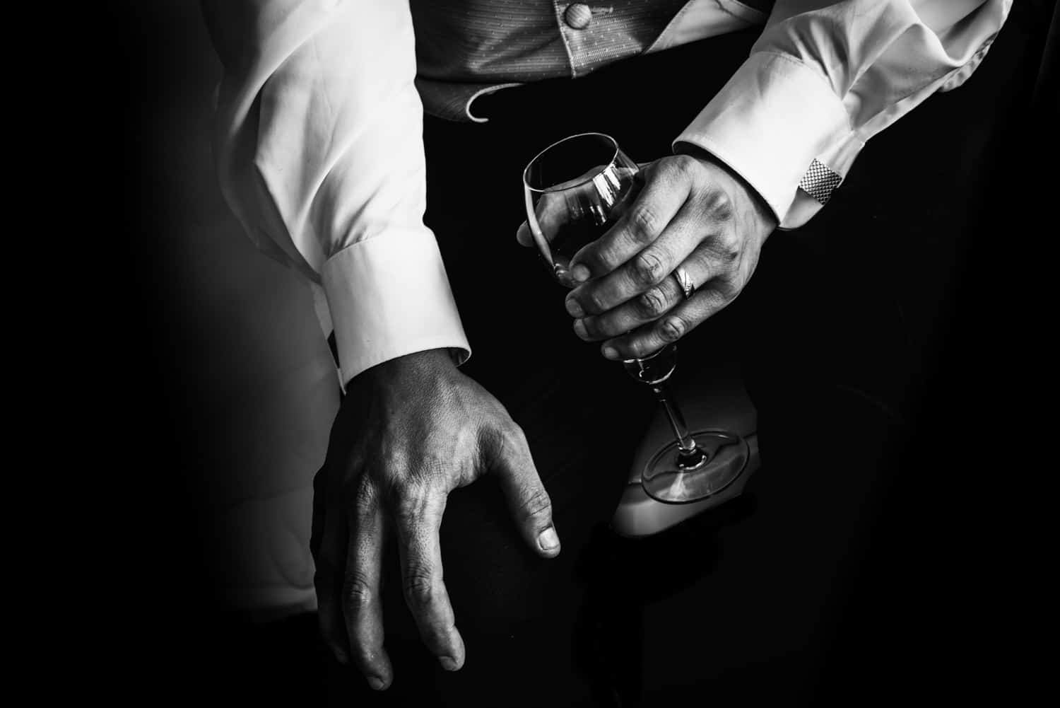 Groom wedding portrait. Black and white, Holding a glass.