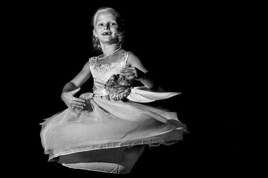 Black and white photograph of flower girl twirling