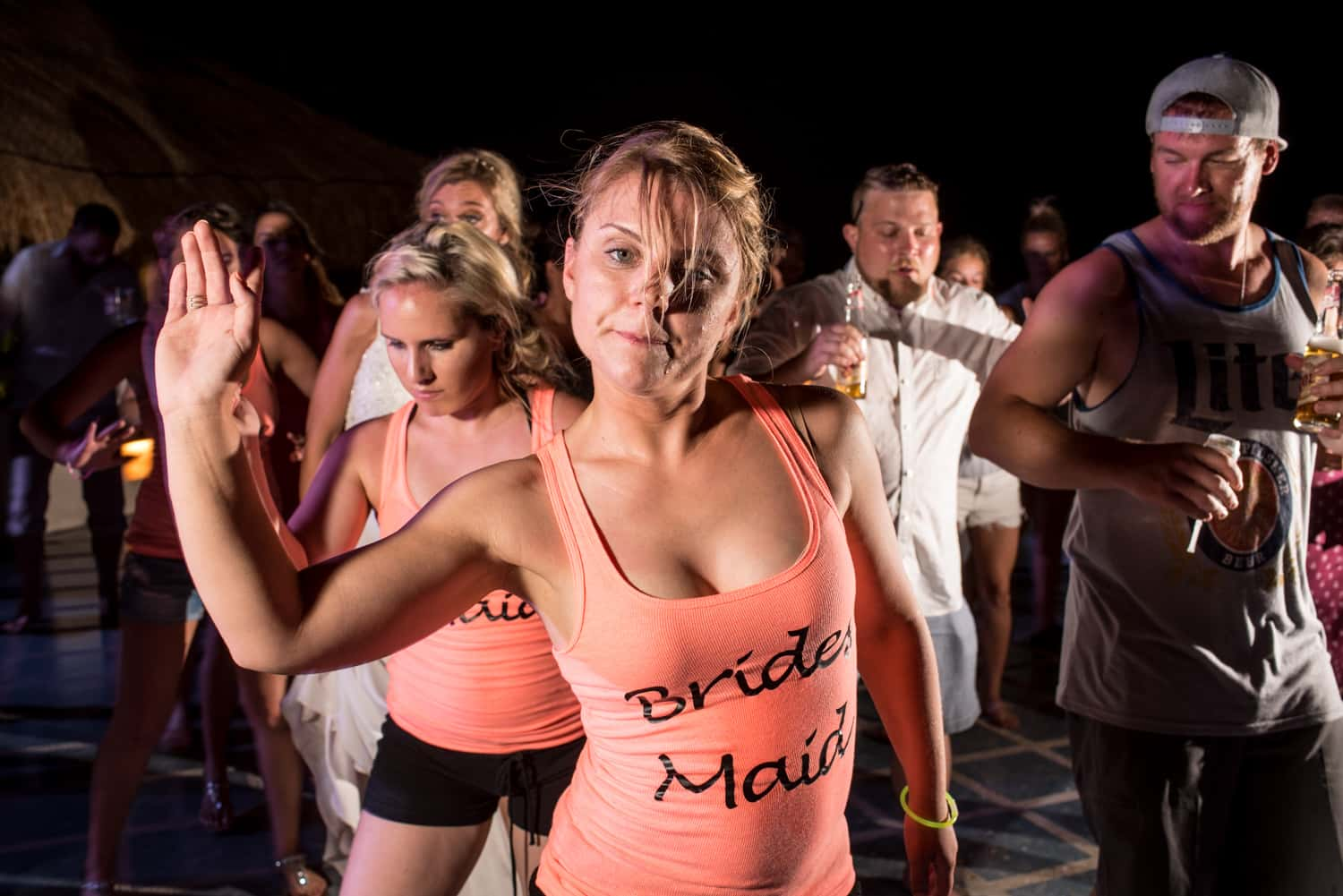 Bridesmaid wearing orange tank top dancing during wedding reception