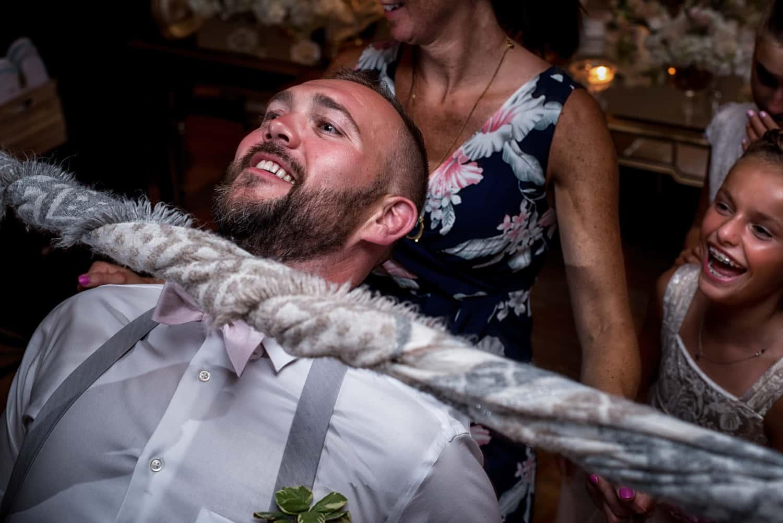 Groomsman going under limbo pole at wedding reception
