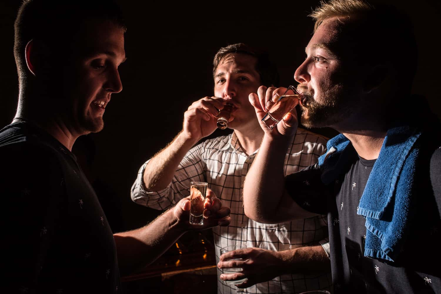 Three men doing tequila shots during wedding reception