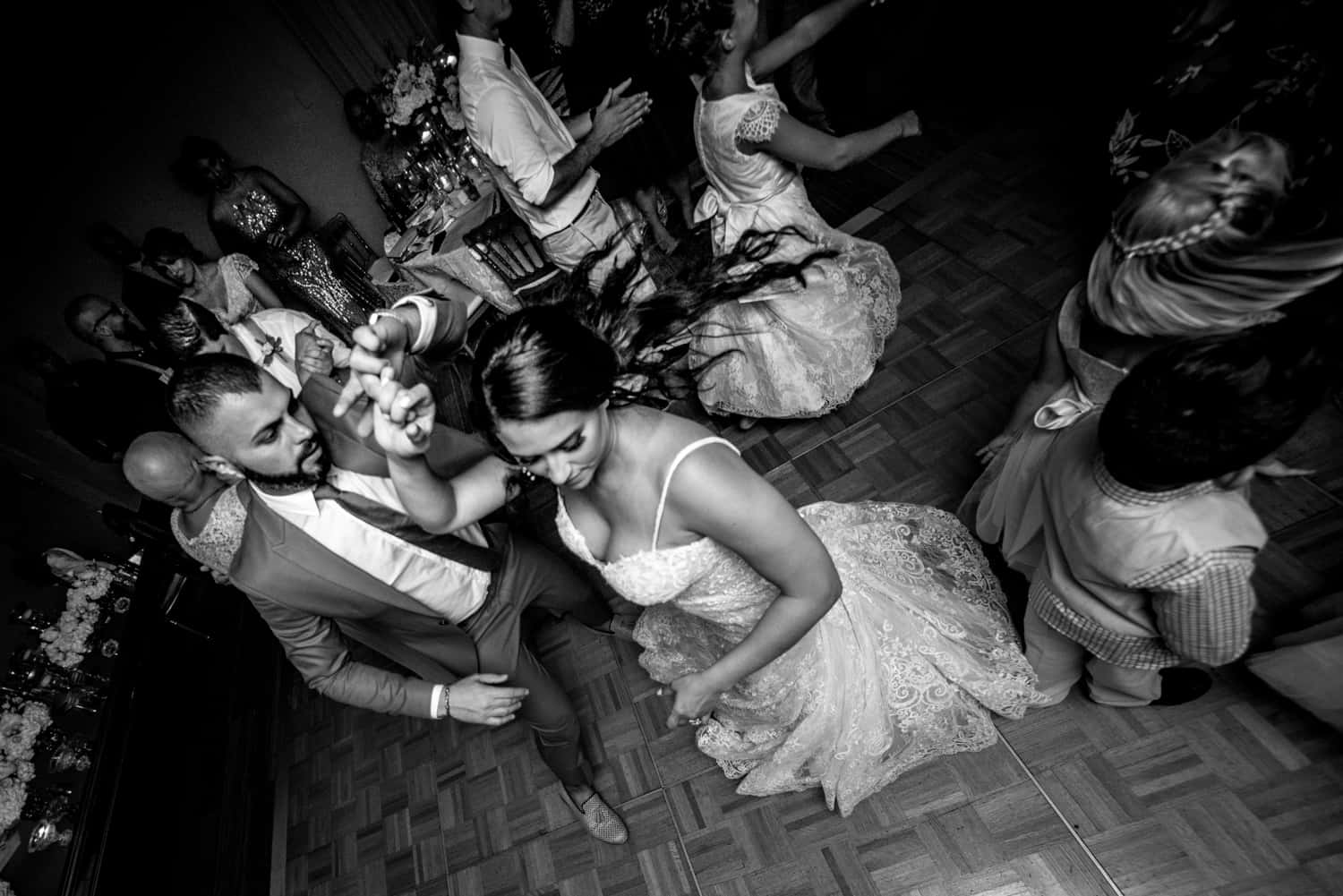 Black and white photograph of a bride dancing during her wedding reception