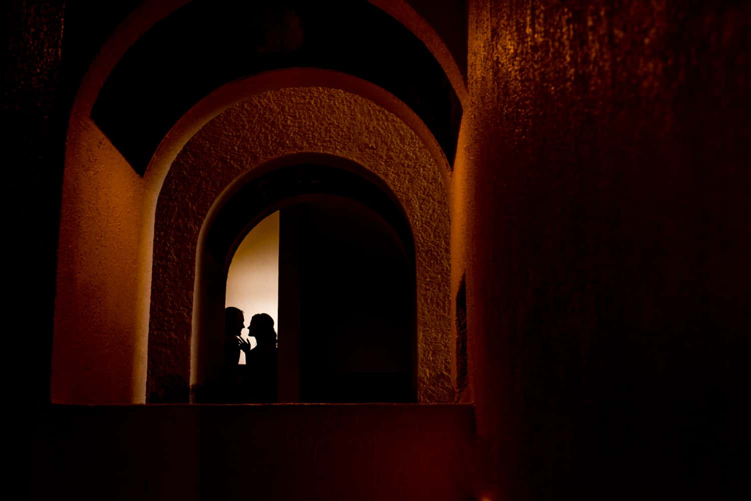 Silhouette portrait of couple under building arches