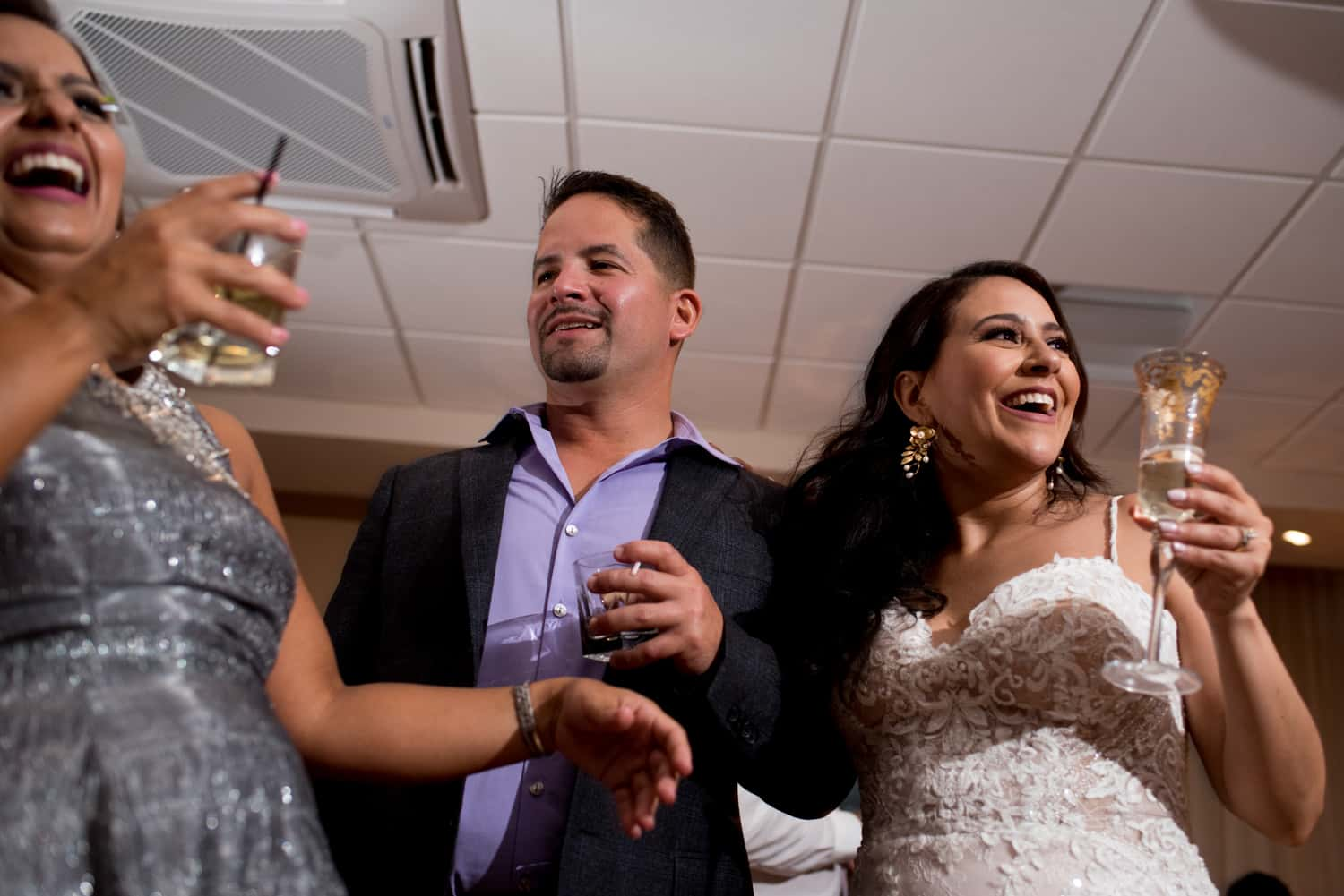 bride holding champagne glass smiling with guests during her wedding reception