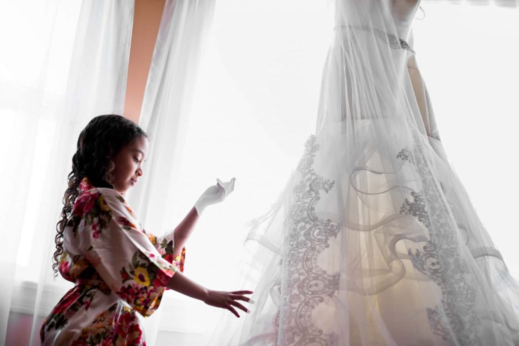 Wedding photograph of a flower girl wearing a floral robe touching a wedding dress hanging in a window.