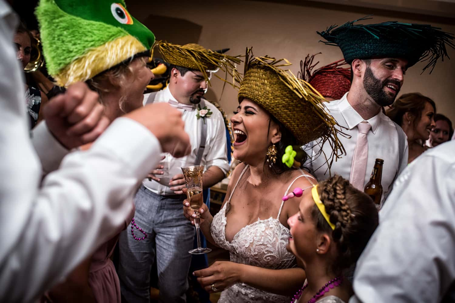 Bride and guests wearing straw hats screaming in excitement