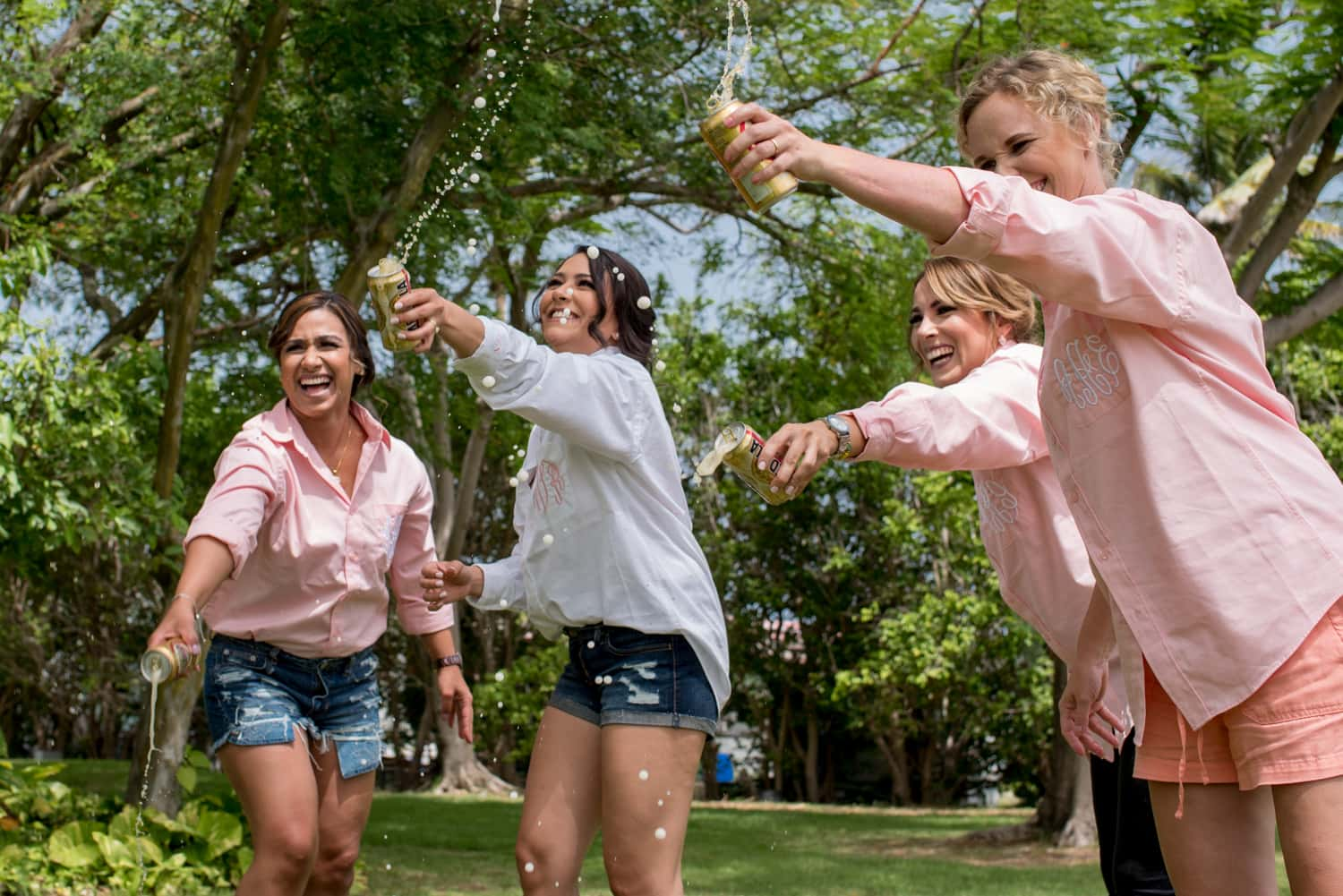 A bride and four of her bridesmaids playfully spraying beer onto the grass for a fun photogrpah