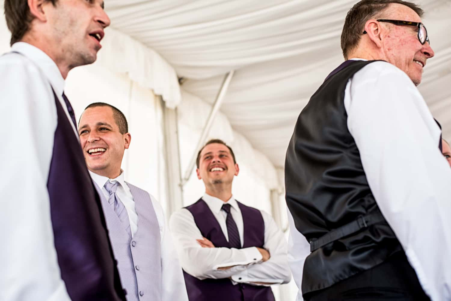 Four groomsmen wearing purple vests and purple ties are all standing talking while looking in different directions.