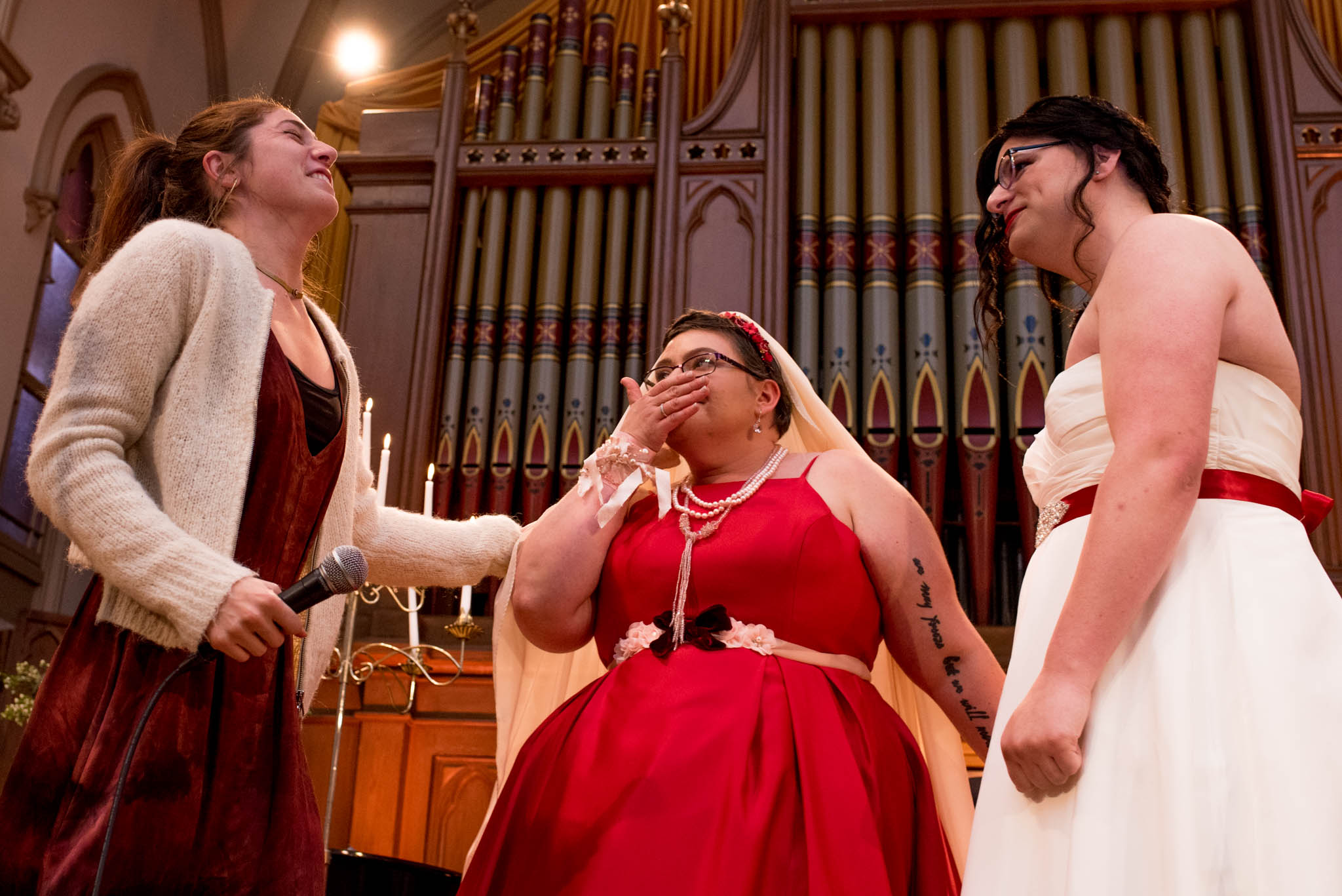 Brides laughing during wedding ceremony in front of old organ