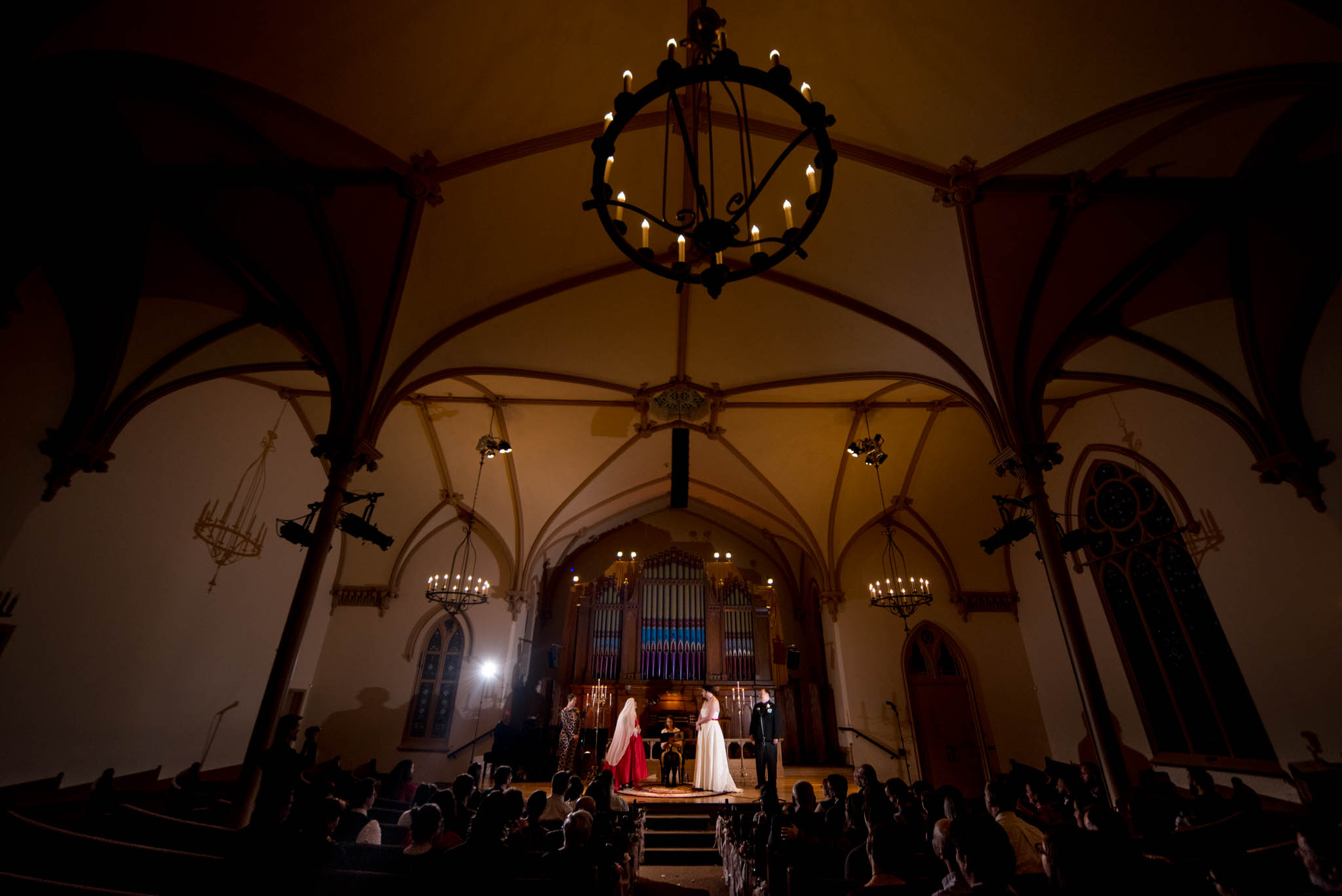 Wide angle photograph of entire church hall during wedding ceremony