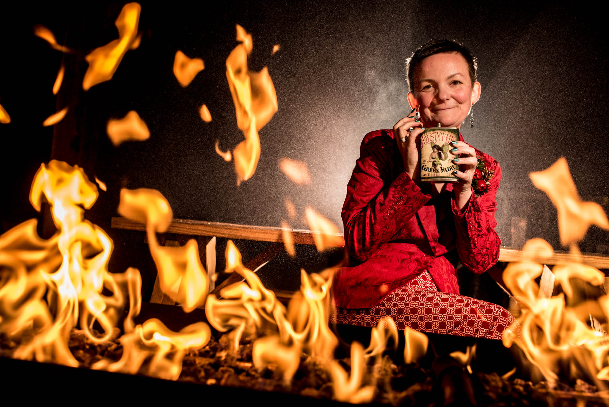 Creative portrait of woman drinking whiskey in front of the fire
