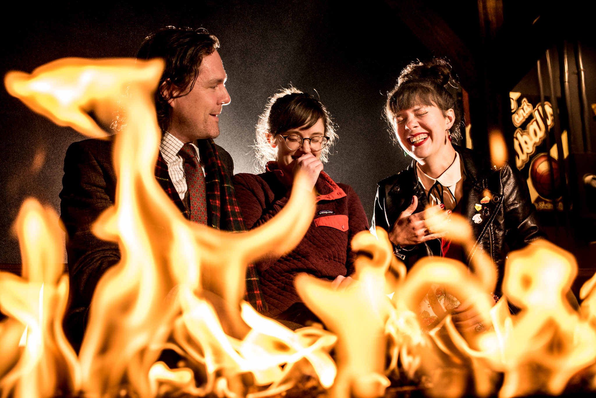 Three wedding guests laughing in front of a fire pit