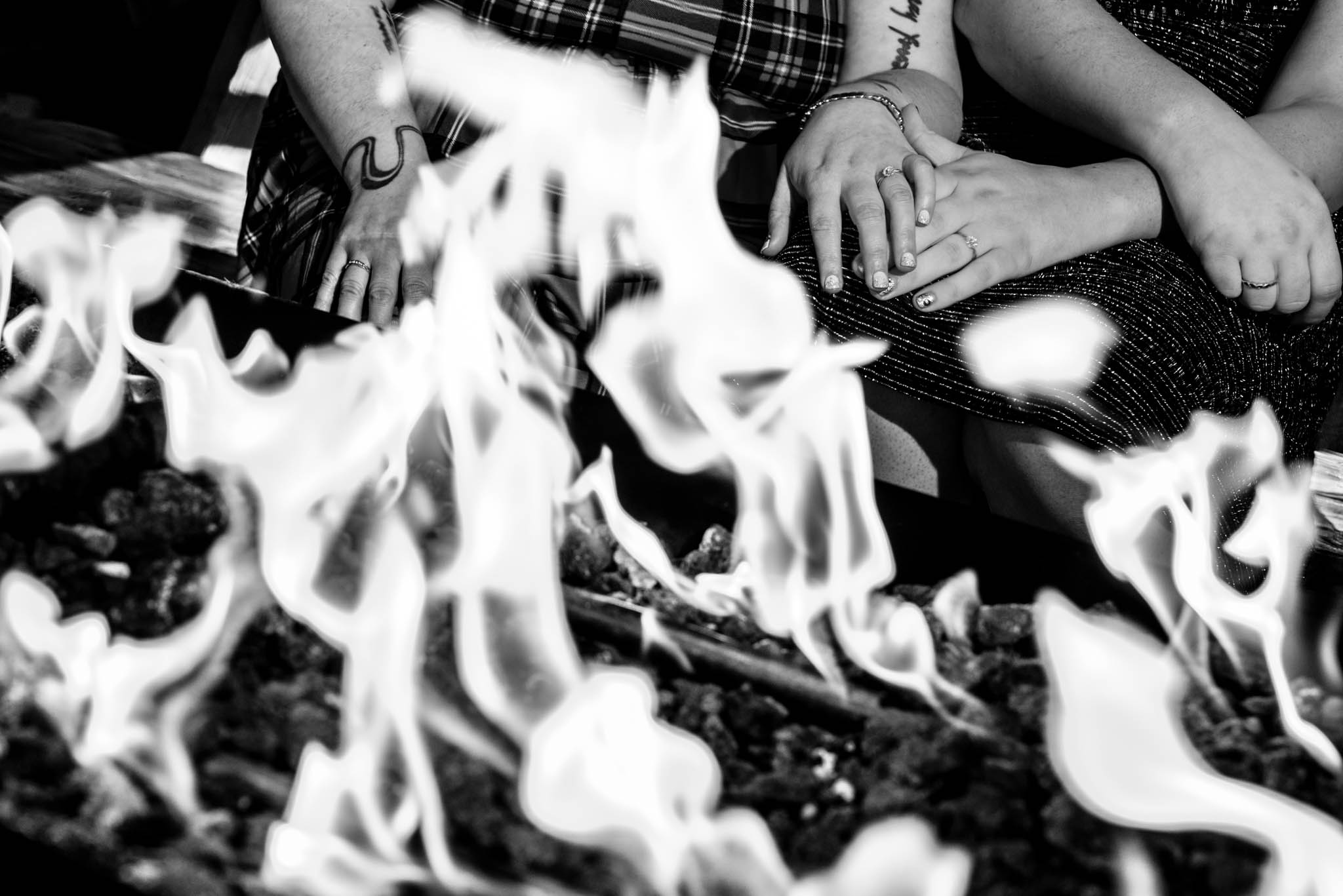 Creative photograph of brides hands with wedding rings in front of the fire