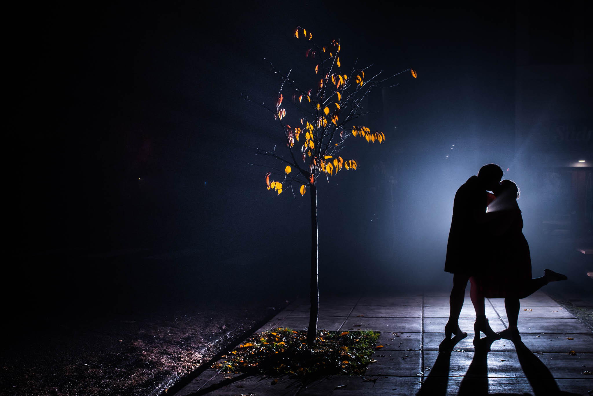Silhouette photograph of wedding couple on misty street