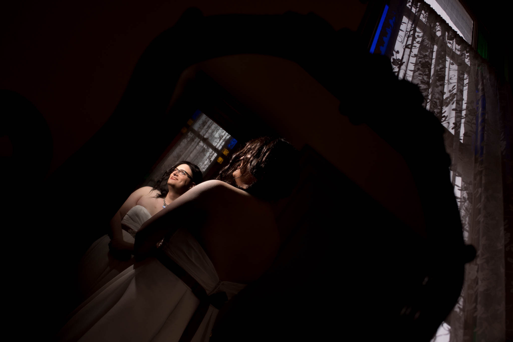 Bride getting ready by stained glass window in The Old Church