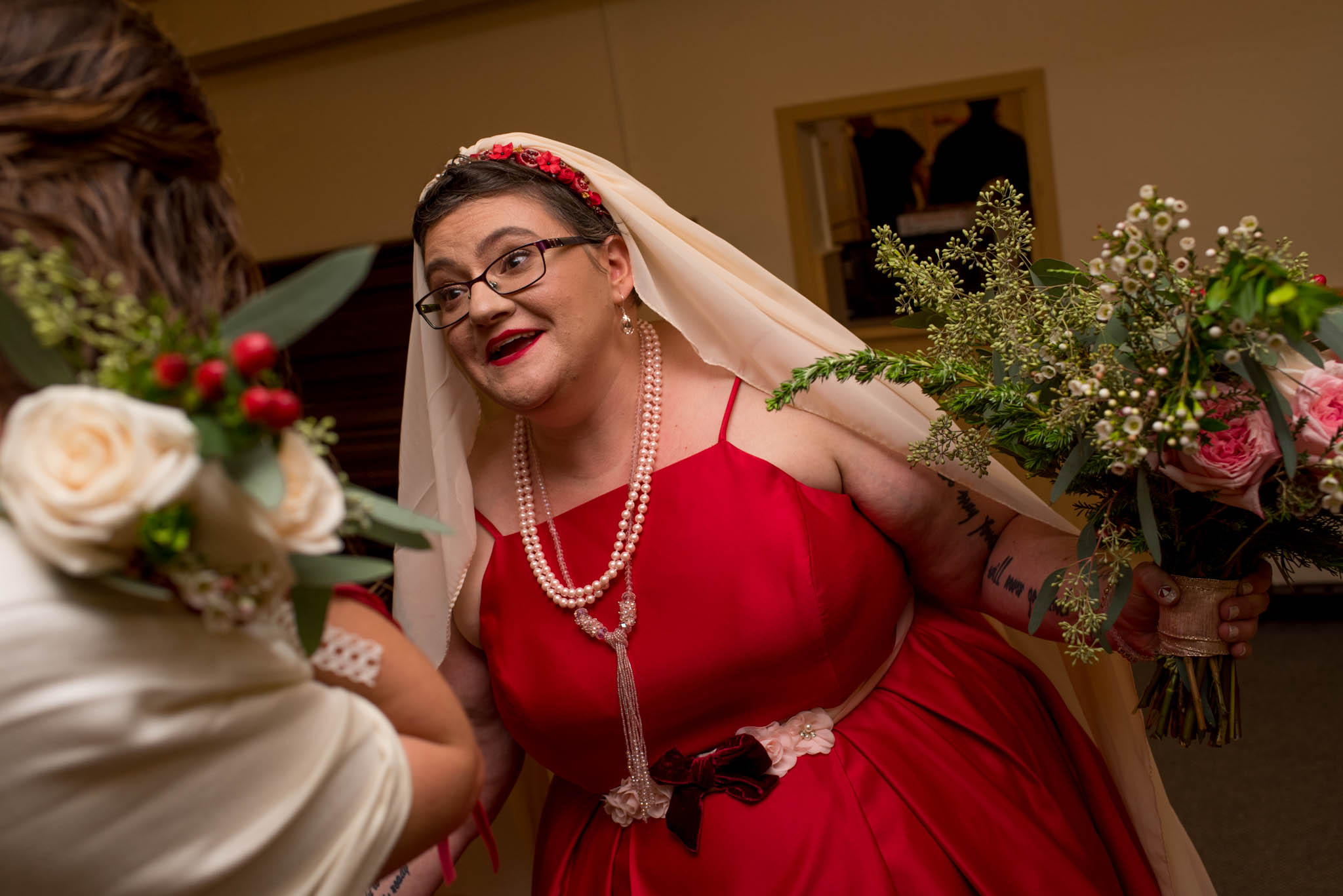 Bride wearing red dress holding bouquet
