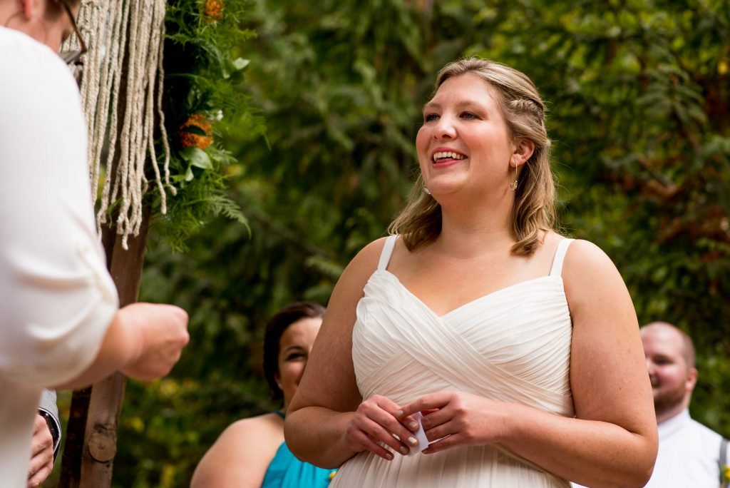 Bride reading her vows in front of green foliage