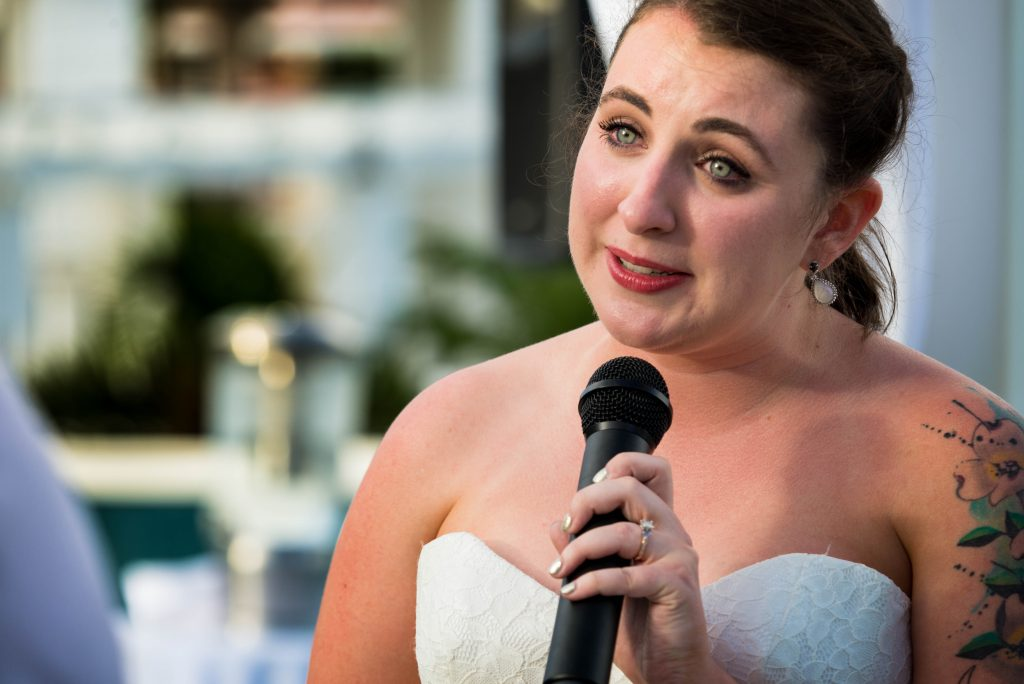 Close up photograph of teary eyed bride reading her vows.