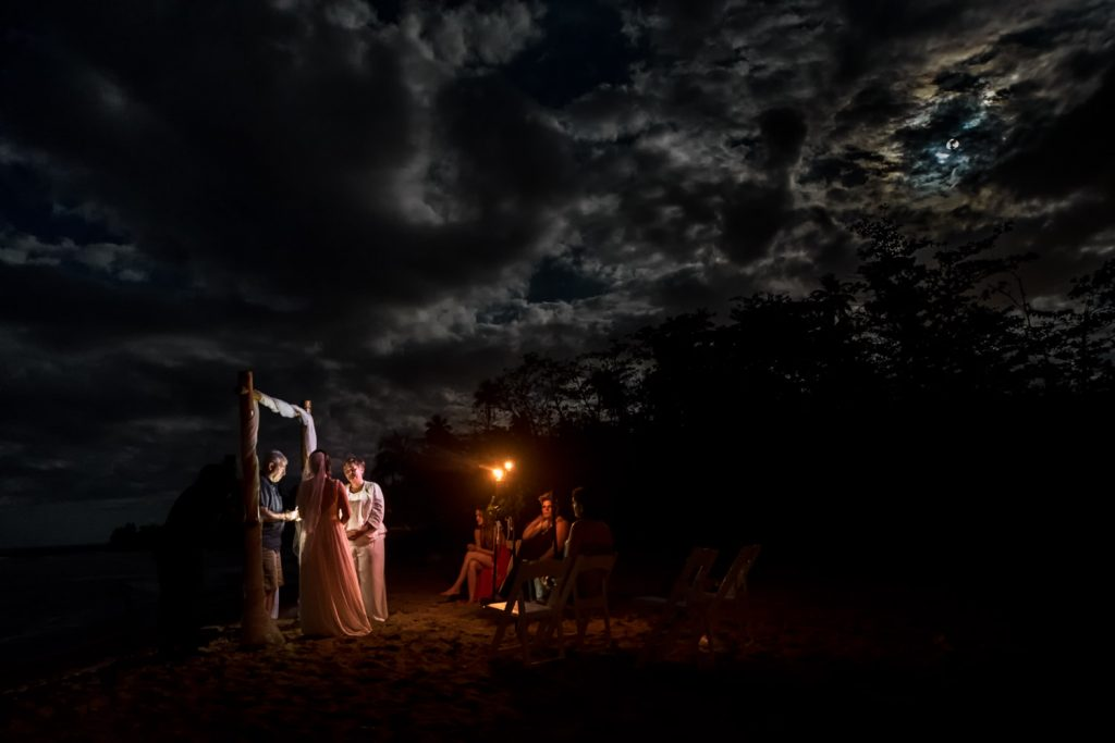 Couple standing during their beach wedding ceremony under the full moon in Rincon Puerto Rico
