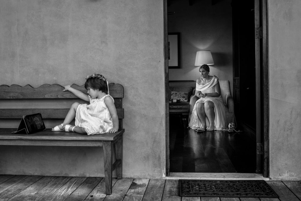Flower girl sitting on a bench watching an ipad at wedding with a bridesmaid in the background.