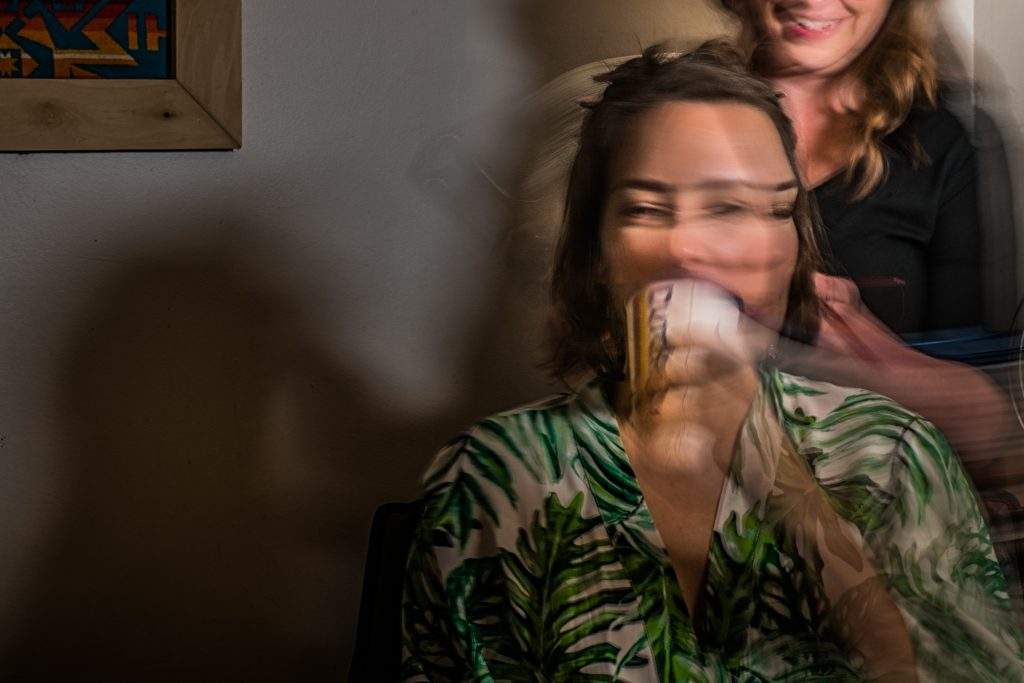 Motion blur photograph of a bride having her hair done on wedding day.