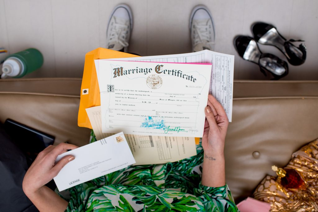 Photograph of a brides hands holding her Marriage Certificate.