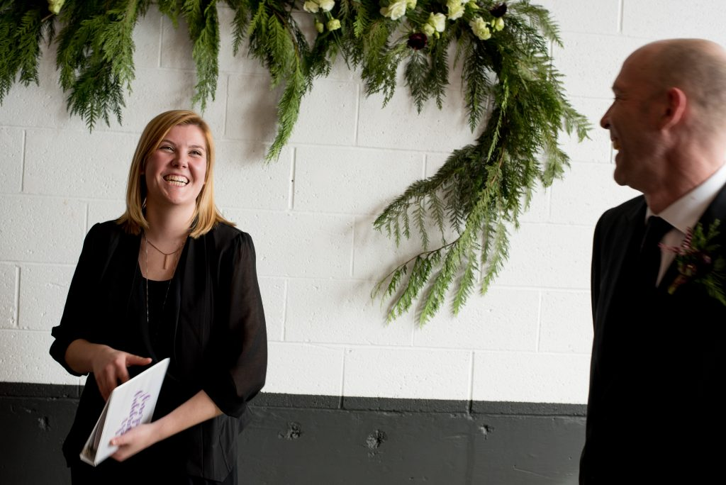 Officiant and groom laughing in front of pine foliage and white flower wedding decorations.