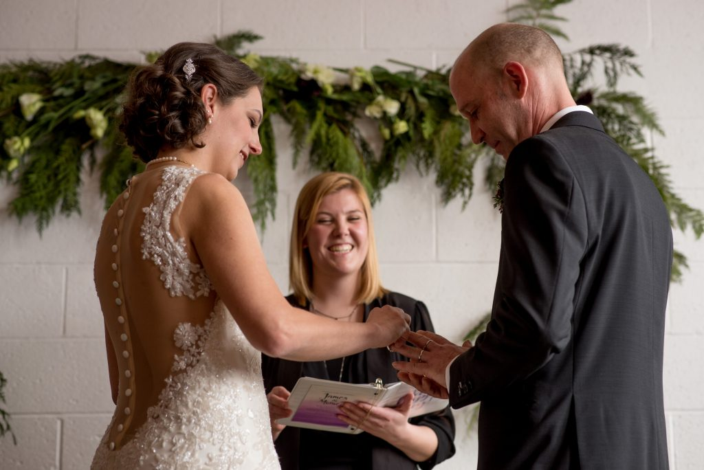 Bride putting the ring onto the grooms finger during their wedding ceremony