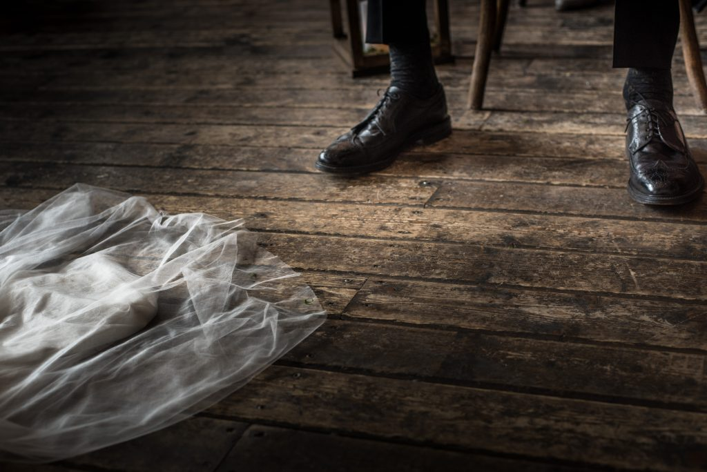 Edge of the brides dress with her fathers shoes on a wooden floor during wedding ceremony