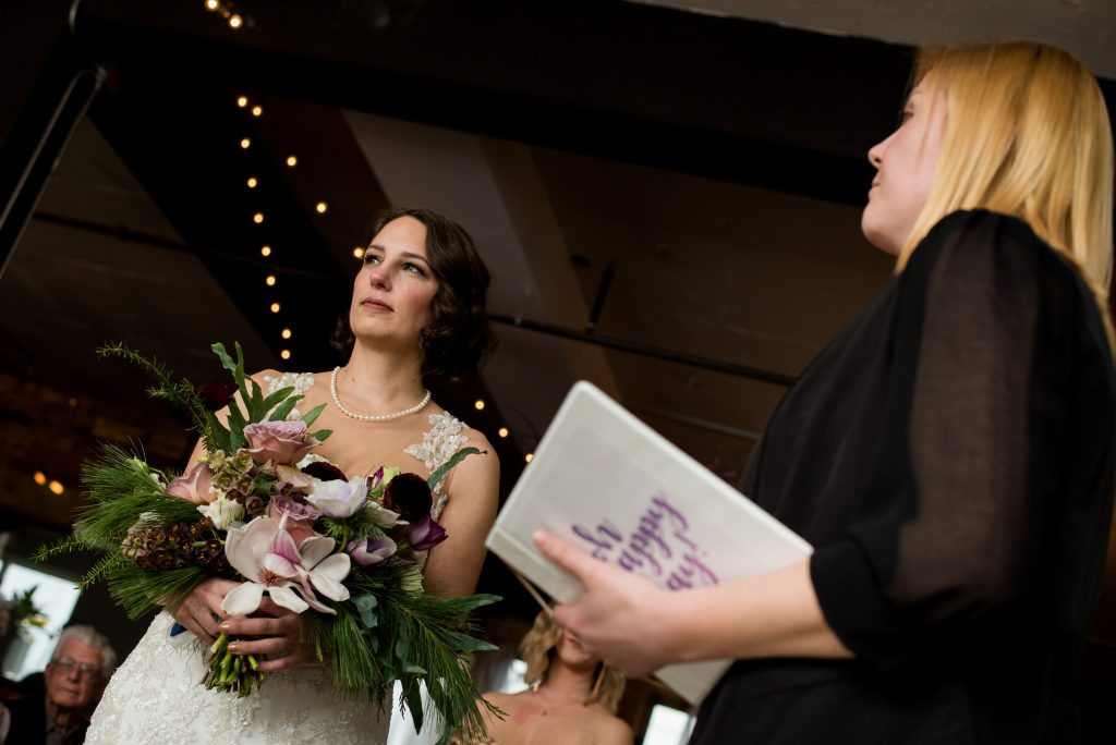 Bride holding bouquet of flowers during wedding ceremony