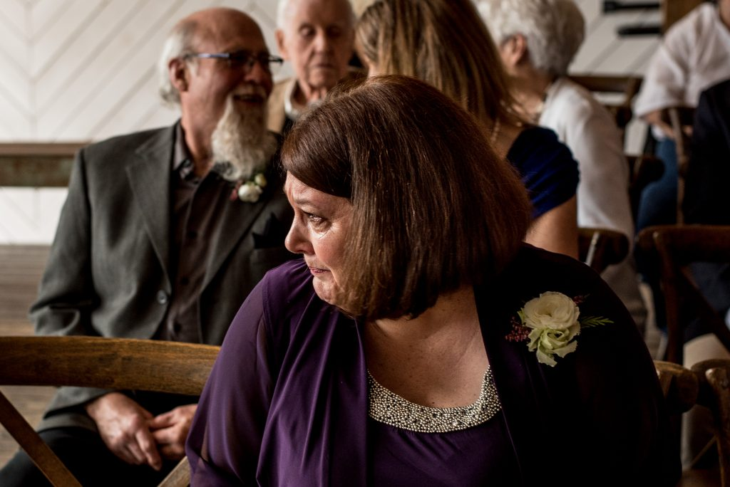 Mother of the bride wearing a purple sweater with wedding flowers crying during the ceremony.