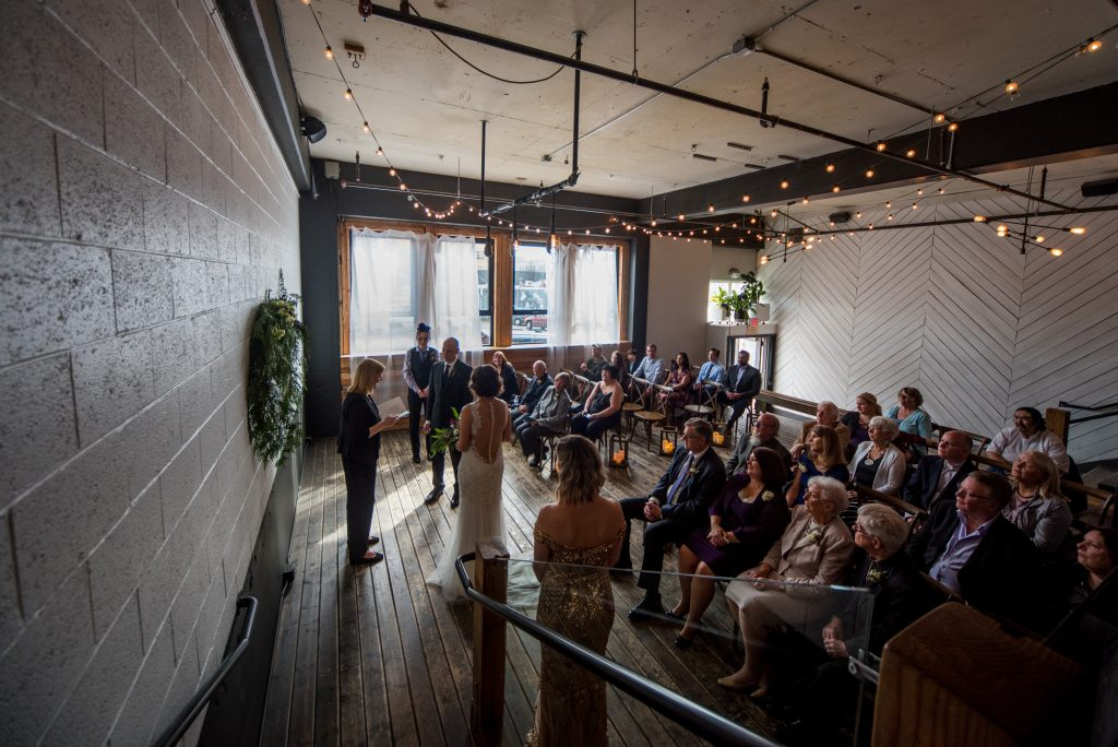 Union pine wedding ceremony filled with people and natural light from the windows.