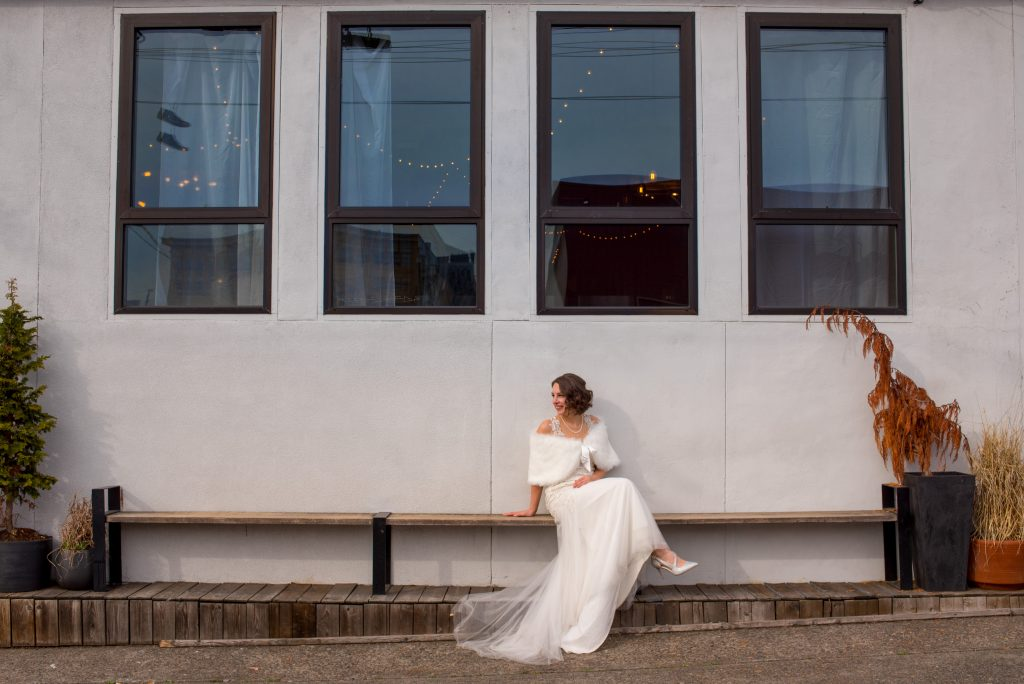 Bride sitting in front of building with four windows.