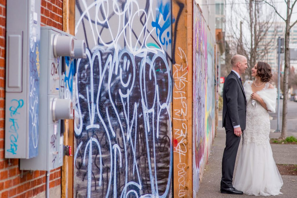Bride and groom standing face to face in front of Grafitti wall.