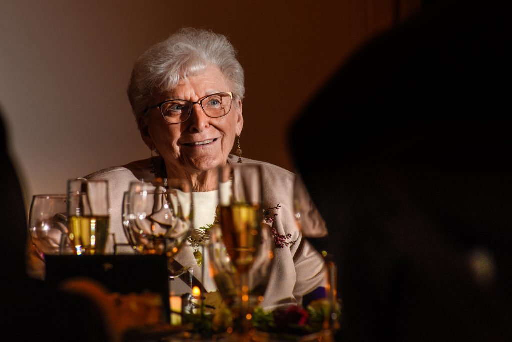 Grandmother smiling siting at a table with wine glasses
