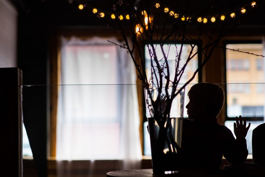 Silhouette of a child playing by flowers during a wedding reception.