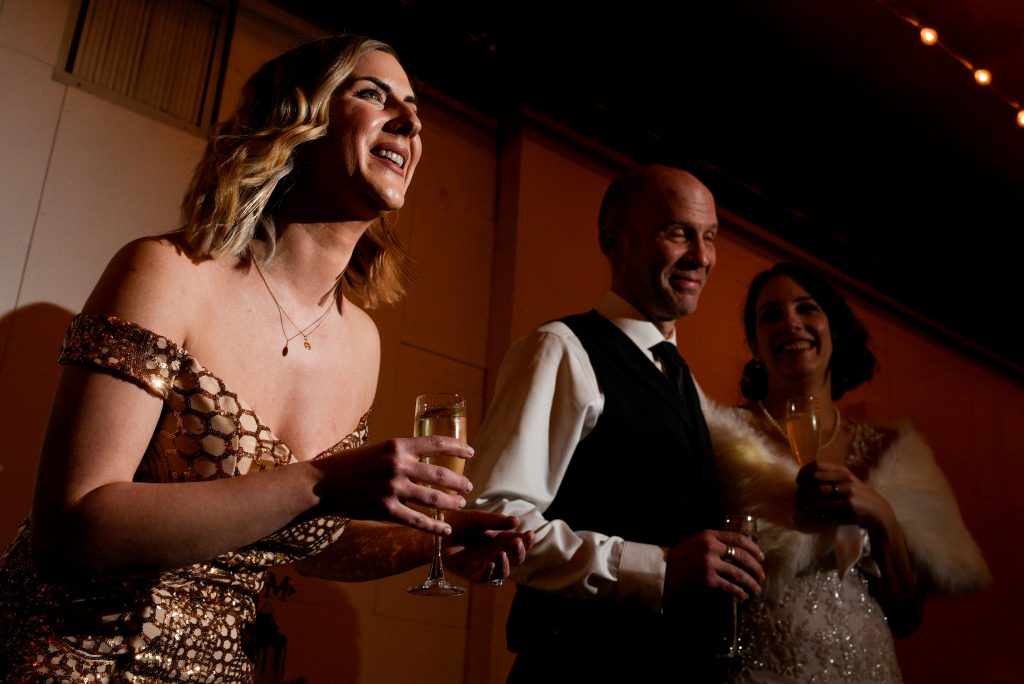 Woman giving a champagne toast standing next to the bride and groom