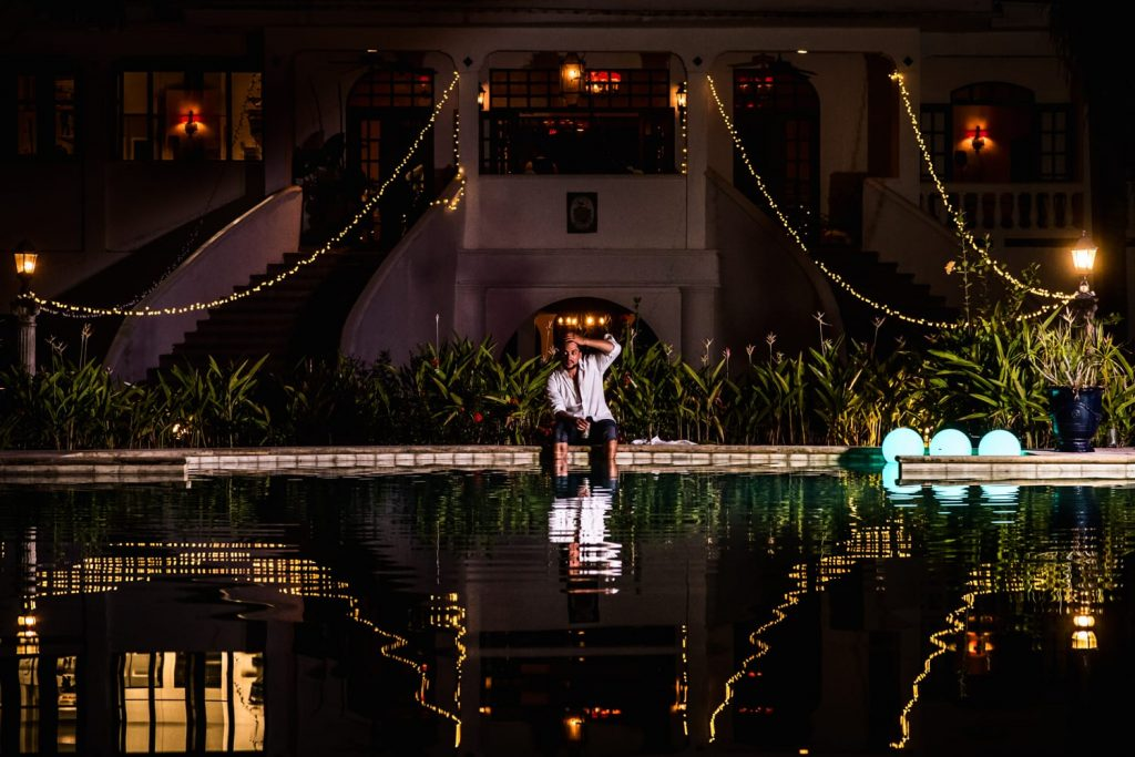 Groom sits with his feet in the pool at the end of  his wedding at the horned dorset in Rincon, Puerto Rico