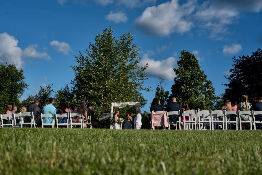 Low angle photograph showing an outdoor wedding ceremony with a bright blue sky and green grass.