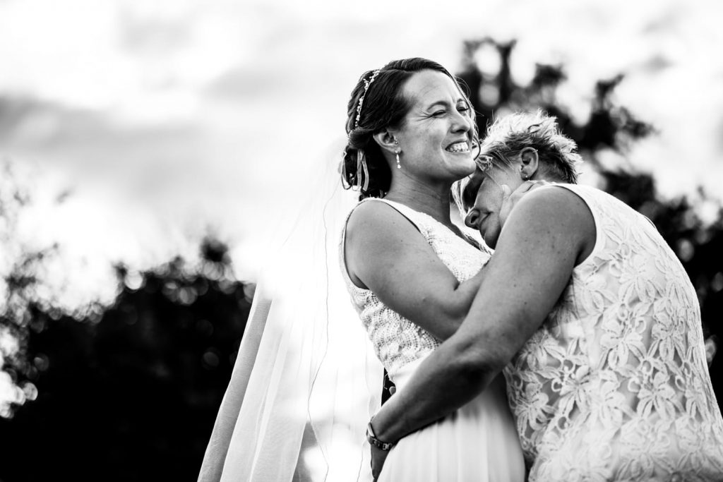 Black and white photograph of two women embracing and smiling on their wedding day one wearing a white wedding dress and the other wearing a floral top.