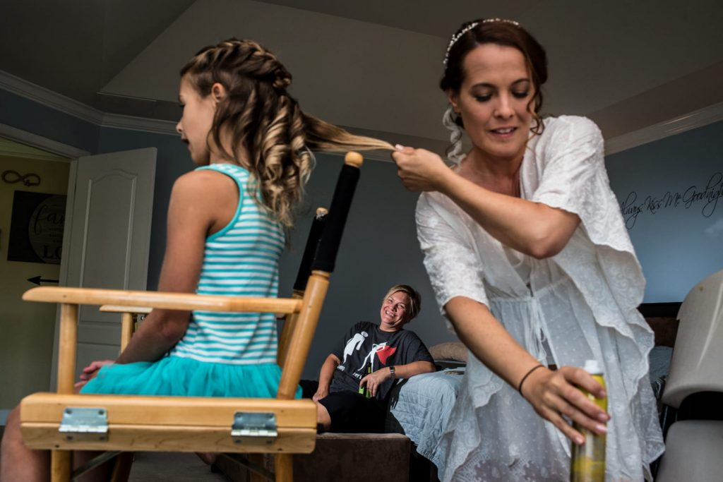 Bride doing young girls hair while her partner watches.