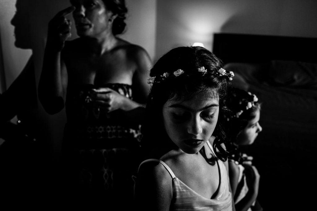 Black and white photograph of flower girls wearing flowers in their hair before the wedding.