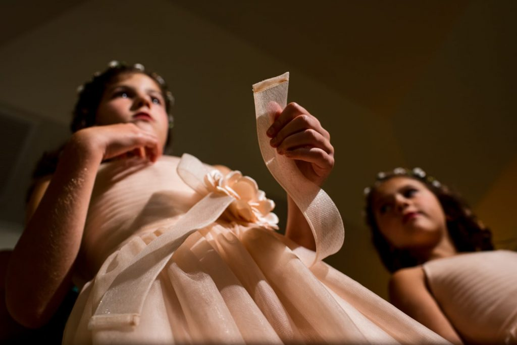 Low angle photograph of two flower girls wearing peach dresses.