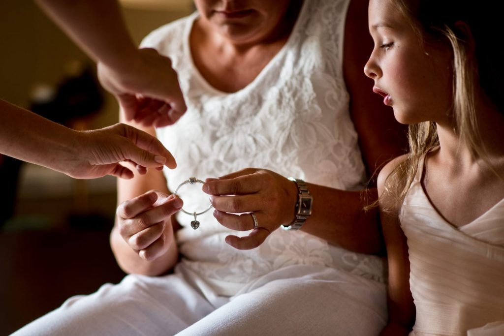 multiple hands holding a silver bracelet while a flower girl looks on.