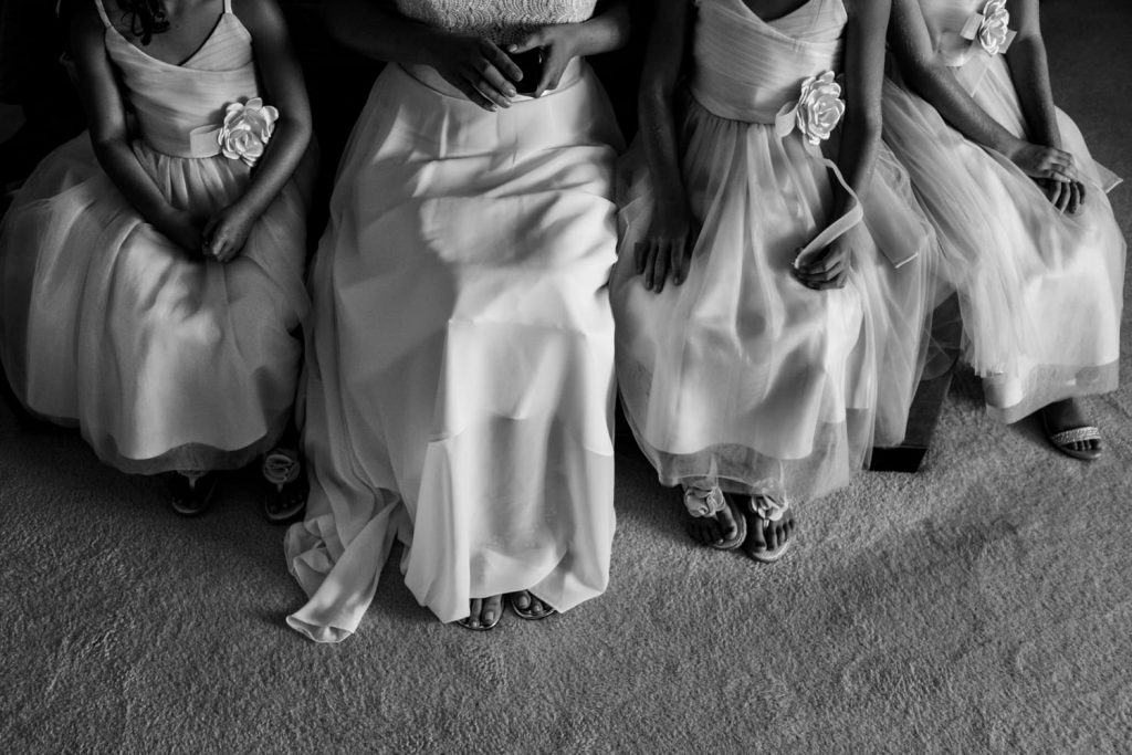 Black and white photograph of the legs of a bride wearing a white dress and three flower girls.